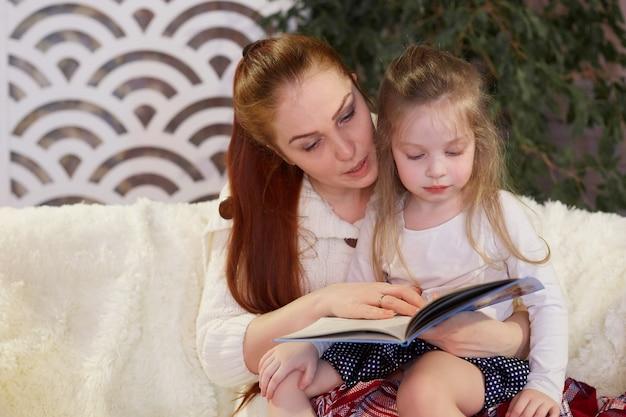 ソファに座って本を読んで彼女の小さな娘の若い美しい母親。