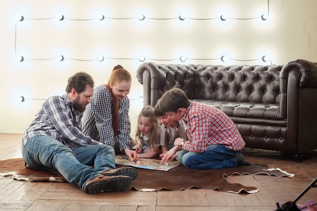Счастливая большая семья играет в настольную игру.