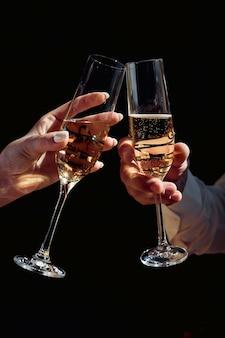 シャンパングラスと男と女のあご、女性と男性の手は暗闇の中でシャンパングラスを保持します