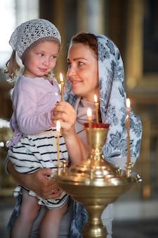 Русская красивая женщина в платке и с рыжими волосами держит маленькую девочку и зажигает свечу перед иконой в русской православной церкви.