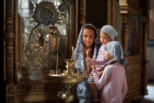 Молодая мать и ее маленькая белокурая кавказская дочь со свечами в православной русской церкви