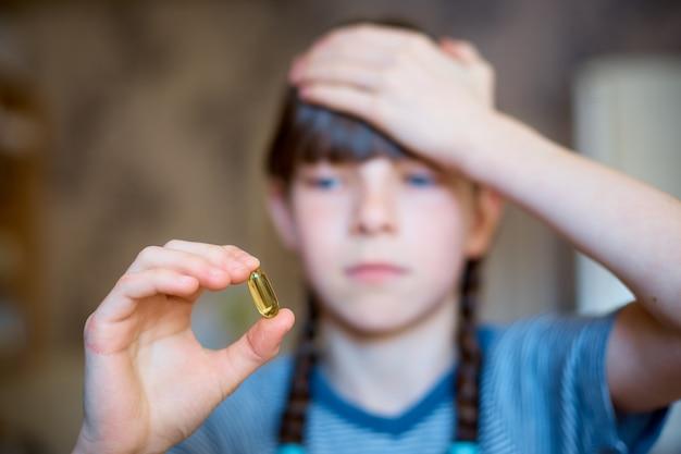 女の子は彼女の手、頭痛、風邪で薬を保持しています。