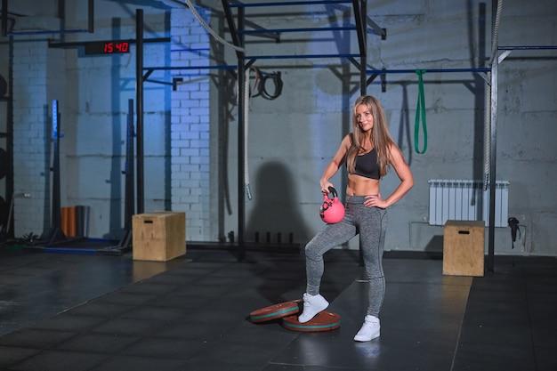 Мускулистая молодая фитнес-блондинка в обтягивающих леггинсах