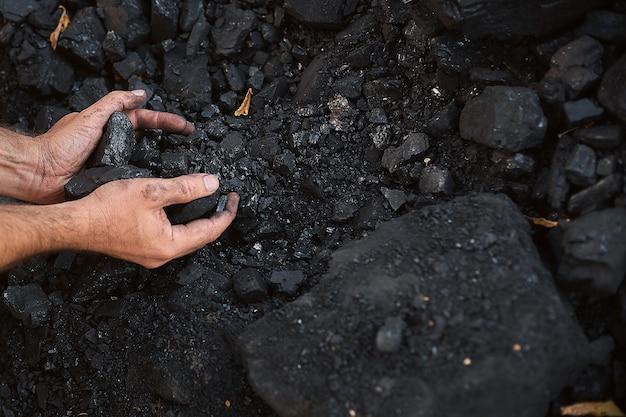 Бедный мужчина средних лет, держась за руки каменного угля для продажи, чтобы обеспечить еду для своей семьи