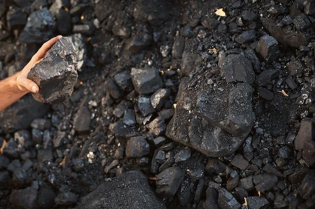 石炭の手を繋いでいる貧しい中年男