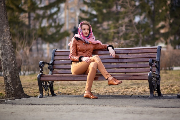 公園のベンチに座ってハンカチを頭と笑顔で持つ美しい若い女性の足の茶色のモカシン