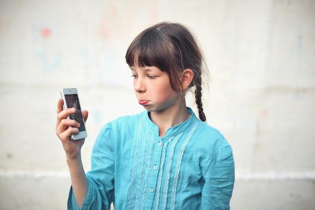動揺して少女、白い背景の手で壊れたガラススクリーンのスマートフォン。
