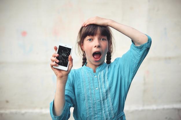 動揺の少女の手で壊れたガラススクリーンのスマートフォン