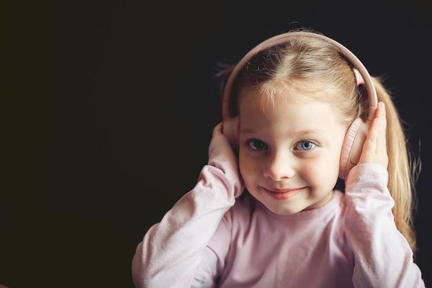 Маленькая девочка в наушниках слушает музыку, портрет кавказского ребенка
