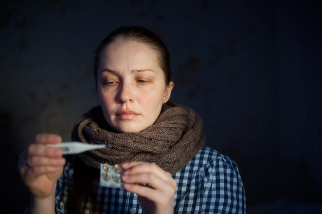 若い女性は、電子体温計で温度を測定します。