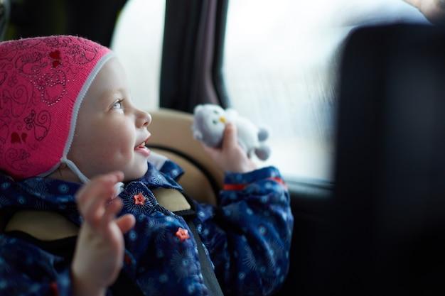 窓で車の後部座席のチャイルドシートに座っている青い目を持つ少女