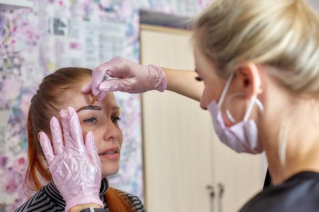 Профессиональный косметолог делает отметку на лице клиента перед татуировкой бровей, перманентным макияжем.
