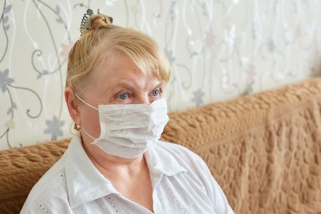 ウイルスと病気から高齢者を保護する、隔離と自己隔離の医療用マスクを着用した高齢者の女性