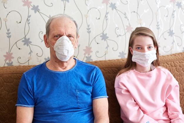 祖父と孫娘の医療用マスクでの検疫。流行時の自己隔離。