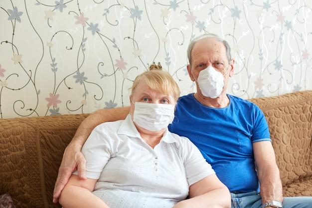 医療用マスクの老夫婦、流行時の高齢者のための自己隔離モード