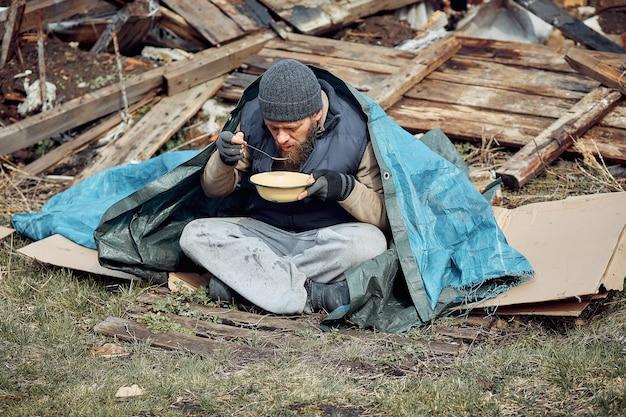 ホームレスの男性が廃墟の近くの皿からスープを食べ、伝染病の最中に貧困層と飢えた人々を助ける