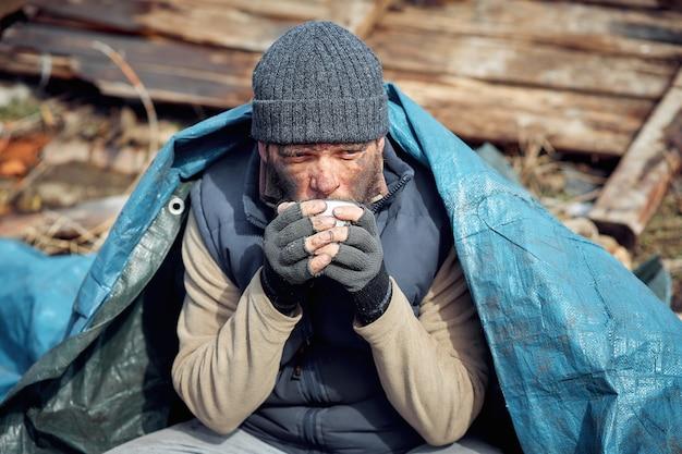 ホームレスの男性が廃墟の近くで熱いお茶を飲み、伝染病の最中に貧しい人々と空腹の人々を助けます