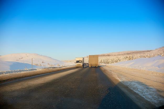 山の中の冬の道。トラックは道路に沿って移動します