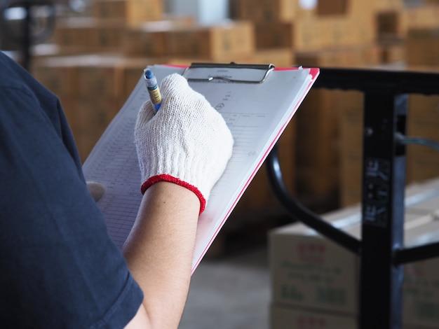 Женский техник проверяет ручной погрузчик поддонов с коробкой на большом складе