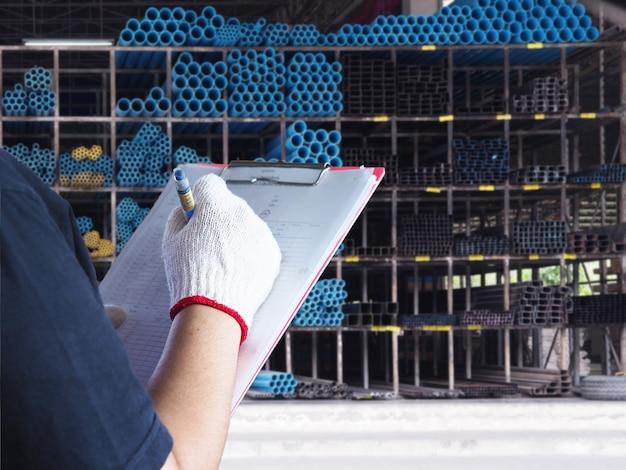 男性の手は、倉庫の塩ビ管と鋼をチェックします。