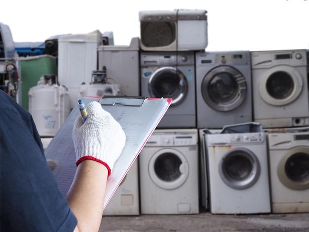 女性はゴミ処理機器の電子機器のリサイクルに取り組んでいます洗濯機は工場産業でのリサイクルのために古く、使用され、使用されなくなった電子機器を廃棄します。