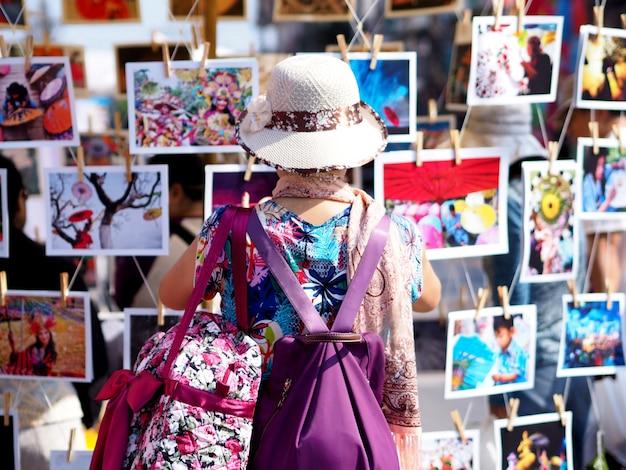 探しているアジアの女性のバックパッカーはタイの観光フェスティバルで観光スポットの写真を見ています。