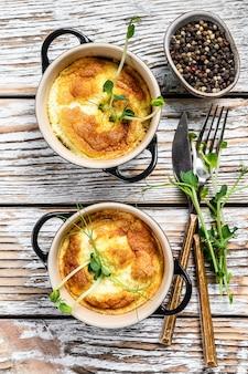 スペインのジャガイモオムレツトルティーヤを鍋でお召し上がりいただけます。白い木製の背景。上面図