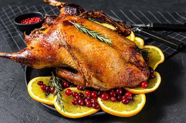 オレンジとロスマリーナを詰めた焼きガチョウ。お祝いテーブル。黒の背景。上面図