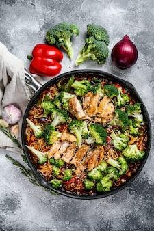 Азиатская яичная лапша с овощами и мясом на сковороде. серый фон вид сверху