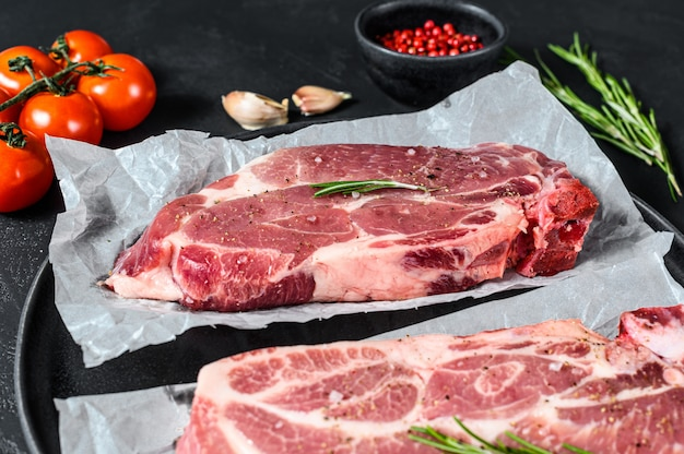 Сырой свиной стейк. мраморное мясо на пергаментной бумаге. черный фон. вид сверху