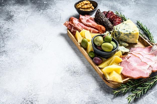 Антипасто с ветчиной, прошутто, салями, голубым сыром, моцареллой и оливками. серый фон вид сверху. пространство для текста