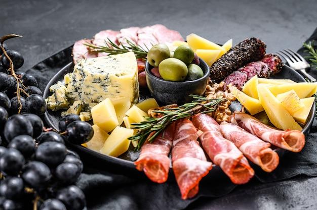 Типичный итальянский антипасто с ветчиной, ветчиной, сыром и оливками. черный фон. вид сверху
