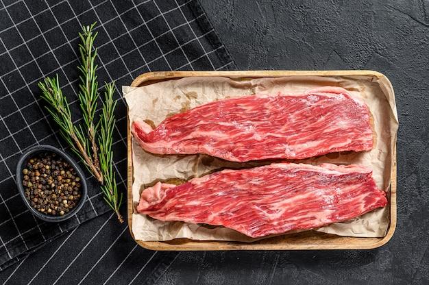 Сырой говяжий стейк, бочка. мраморная говядина. черный фон. вид сверху