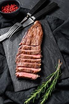 ローストミディアムレアスライスフランクビーフステーキ。黒の背景。上面図