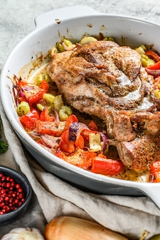 グラタン皿に野菜と七面鳥のもも肉を焼いた。灰色の背景。上面図