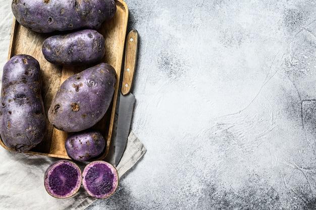 Вителотте сырой картофель на разделочной доске. серый фон вид сверху. пространство для текста