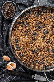 キノコとそばのお粥。ビーガンフード。ロシア、ウクライナ料理。黒の背景。上面図。コピースペース