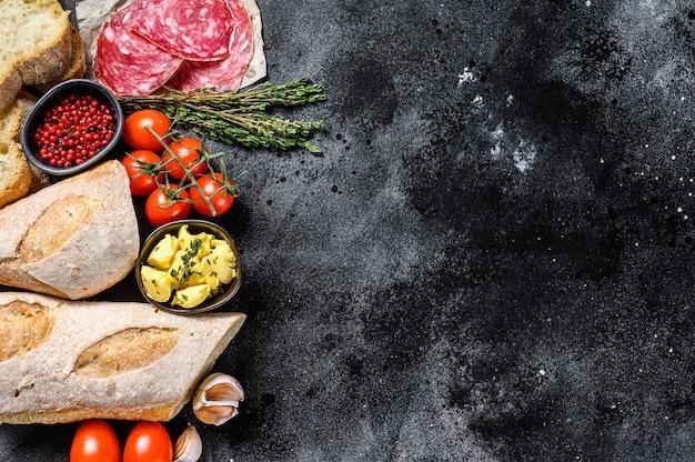 バゲットサンドイッチの材料-ハム、サラミ、チーズ、バター、トマト。黒の背景。上面図。コピースペース