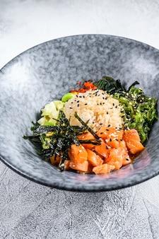 Посыпать миску сырым лососем, рисом и овощами. серый фон вид сверху