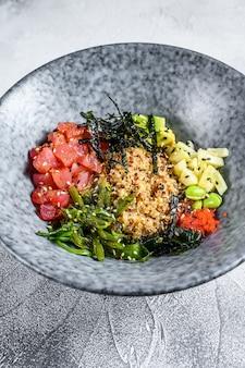 Тыкать миску с сырым тунцом и овощами. гавайское блюдо. концепция здорового питания. серый фон вид сверху