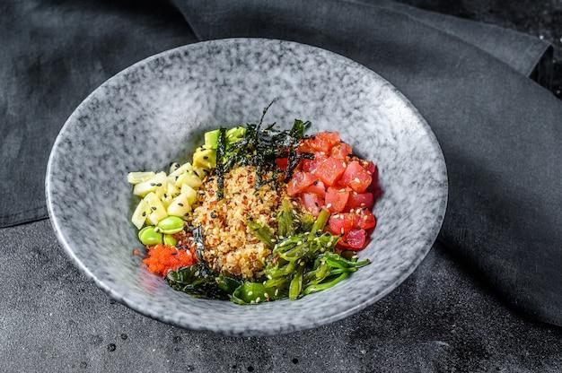 Тыкать миску с сырым тунцом и овощами. гавайское блюдо. концепция здорового питания. черный фон. вид сверху