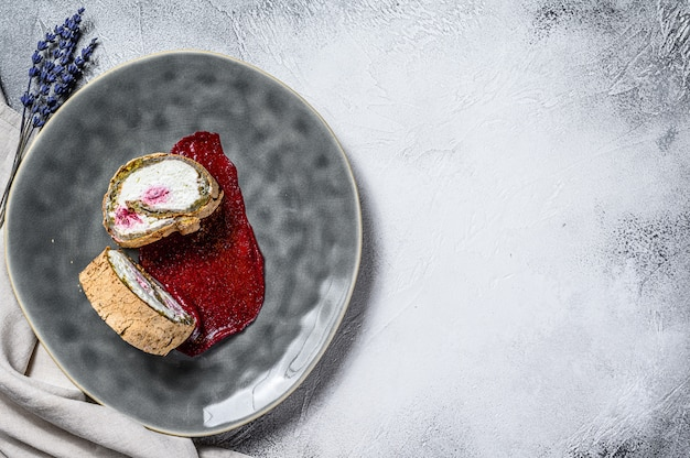 Ломтик десертного рулета с клубничным джемом и сливками. серый фон вид сверху. копировать пространство