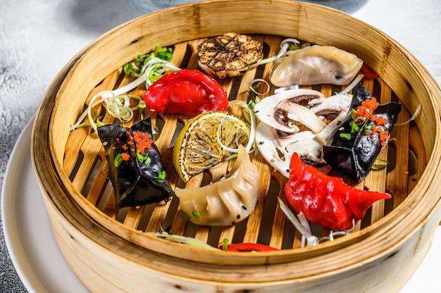 伝統的な竹蒸し器で自家製中国と韓国の餃子を提供しています。灰色の背景。上面図