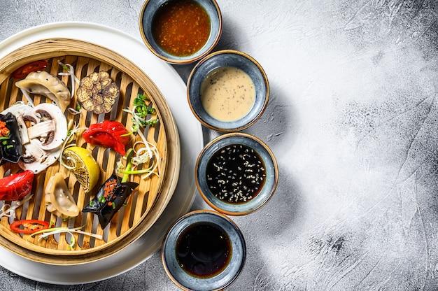 伝統的な竹蒸し器で自家製中国と韓国の餃子を提供しています。灰色の背景。上面図。コピースペース