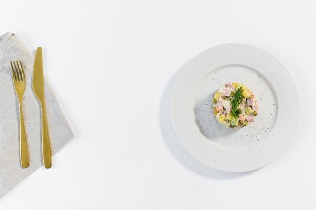 Русский салат на белой тарелке с золотым ножом и вилкой
