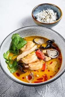 エビとココナッツミルクのトムヤムスープ。灰色の背景。上面図