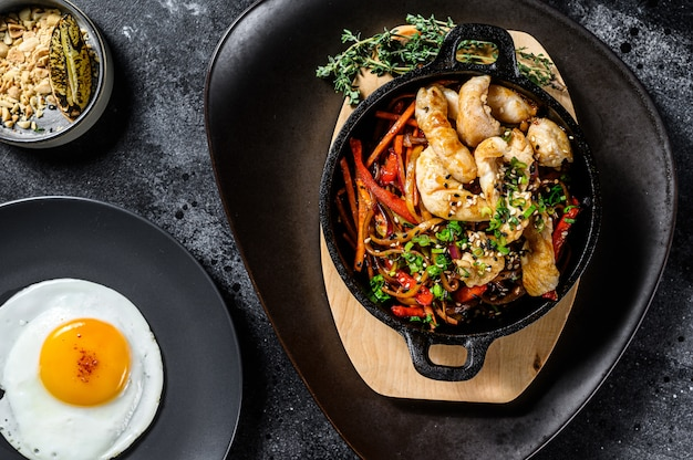 Удон поджарить на сковороде лапшу с курицей и овощами. черный фон. вид сверху
