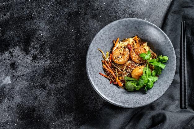 海老と野菜を炒めたライスヌードル。アジアの中華鍋。黒の背景。上面図。コピースペース