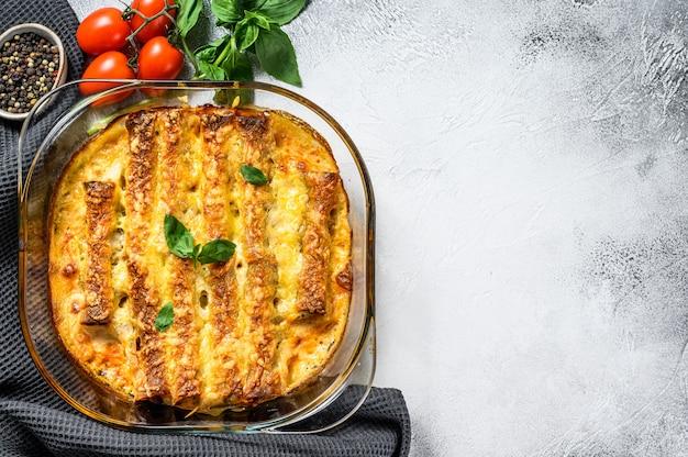 Каннеллони фаршированные соусом бешамель. макароны запеченные с мясом говядины, сливочным соусом, сыром. серый фон вид сверху. копировать пространство