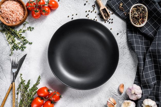 Черная пустая плита в центре свежих сырцовых зеленых цветов, овощей. здоровое, чистое питание, веганский, диета еда концепция. белый фон. вид сверху. копировать пространство